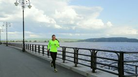 Caucasian brunette woman in sports cloth runs on embankment near the river stock video footage