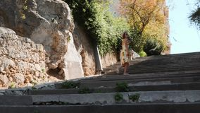 Caucasian brunette woman walking on concrete staircase and looking at the architecture. Young girl climbing steps.  stock video footage