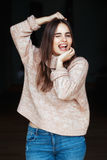 Caucasian brunette young beautiful girl woman model with long dark hair and brown eyes in turtleneck sweater and blue jeans. Portrait of funny white Caucasian stock image