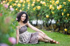 Caucasian brunette young woman sitting on green grass in a rose garden near yellow roses bush, smiling with teeth, looking to the stock image