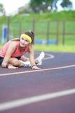 Caucasian brunettkvinnlig i idrotts- Sportgear som har ben som utomhus sträcker Excercises Royaltyfri Fotografi