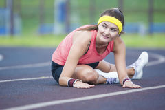 Caucasian brunettkvinnlig i idrotts- Sportgear som har ben som utomhus sträcker Excercises Arkivfoto