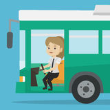 Caucasian bus driver sitting at steering wheel. Caucasian female bus driver sitting at steering wheel. Young female driver driving passenger bus. Female bus Royalty Free Stock Photography