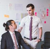 Caucasian business executive praising subordinate by giving a pat on the shoulder with eye contact.  Stock Photography