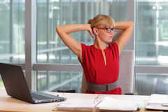 Caucasian business woman in eyeglasses relaxing neck,stretching arms Stock Images