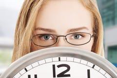 Caucasian business woman holding clock. Royalty Free Stock Photos