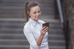 Caucasian Business Woman With Smartphone and Wearing Wireless Headphones. Royalty Free Stock Images