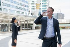 Caucasian businessman and Asian business woman standing and drinking pure mineral water from plastic bottle. Caucasian businessman and Asian business women Royalty Free Stock Photos