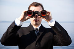 Caucasian businessman with binoculars Stock Photo