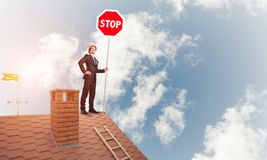 Caucasian businessman on brick house roof showing stop road sign Stock Photo