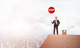 Caucasian businessman on brick house roof showing stop road sign. Mixed media Stock Images