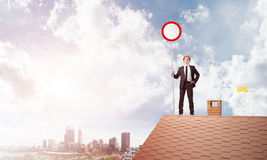 Caucasian businessman on brick house roof showing stop road sign. Mixed media Stock Image