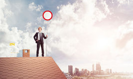 Caucasian businessman on brick house roof showing stop road sign Stock Images