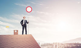 Caucasian businessman on brick house roof showing stop road sign Royalty Free Stock Photography