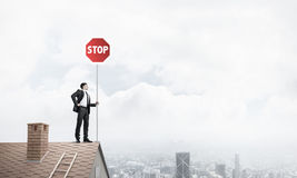 Caucasian businessman on brick house roof showing stop road sign Stock Photography