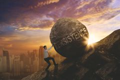 Caucasian businessman pushing persistence word. Caucasian businessman climbing on the cliff while pushing a stone with persistence word. Shot at sunrise time Royalty Free Stock Photography
