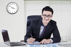 Caucasian businessman with clock in office Royalty Free Stock Images