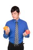Caucasian businessman comparing apple to orange. Isolated studio shot of a Caucasian man looking down comparing an apple to an orange stock photography