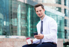 Caucasian businessman having his lunch break with coffee and mob Royalty Free Stock Images