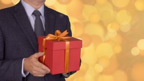 Caucasian businessman hold and give red gift box. From unfocus to focus motion. Adult man in classic business suit hold stock video