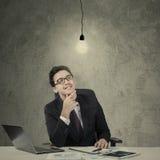 Caucasian businessman looking at lamp Stock Photos