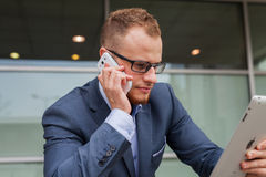 Caucasian businessman outside office using mobile phone and tabl Royalty Free Stock Photography
