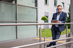 Caucasian businessman outside office using white tablet pc on a Royalty Free Stock Photos