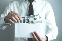 Caucasian businessman putting hundred dollars in envelope. royalty free stock photography