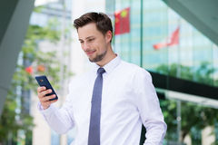 Caucasian businessman read on the cellphone. At outdoor Royalty Free Stock Photography