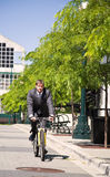 Caucasian businessman riding a bicycle Stock Image
