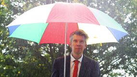 Caucasian businessman sheltering under a colourful umbrella. In the torrential rain ideas of protection adversity struggle stock video footage