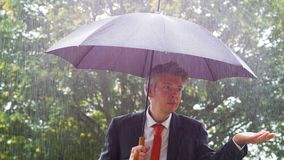 Caucasian businessman sheltering underneath an umbrella in the rain. Caucasian businessman sheltering underneath an umbrella in the torrential rain ideas of stock video