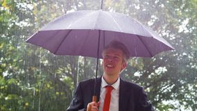 Caucasian businessman sheltering underneath an umbrella in the rain. Caucasian businessman sheltering underneath an umbrella in the torrential rain ideas of stock video footage
