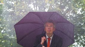 Caucasian businessman sheltering underneath an umbrella in the rain. Caucasian businessman sheltering underneath an umbrella in the torrential rain ideas of stock footage