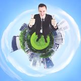 Caucasian businessman showing thumbs up. Top view of a Caucasian businessman showing thumbs up while standing in the 3d city Stock Photos