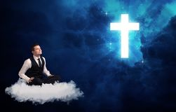 Man sitting on cloud lokking at a cross Stock Photography