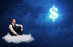 Man sitting on a cloud dreaming of money. Caucasian businessman sitting on a white fluffy cloud wondering about huge money sign royalty free stock photography