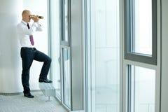 caucasian businessman spying using telescope thru office window Stock Image