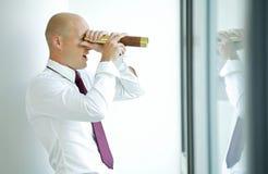 caucasian businessman spying using telescope thru office window Stock Photo