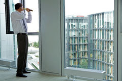 Caucasian businessman spying using telescope thru office window Royalty Free Stock Images