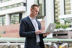 Caucasian businessman stand and typing word into laptop Royalty Free Stock Photography
