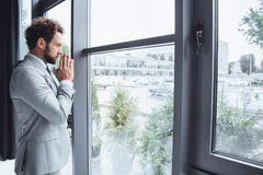 Caucasian businessman standing at window in office and praying Royalty Free Stock Image