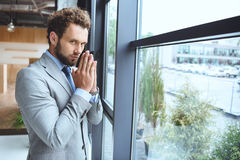 Caucasian businessman standing at window in office and praying Stock Images