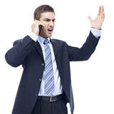 Caucasian businessman talking on cellphone. Caucasian business person talking on cellphone, angry, furious, isolated on white background Royalty Free Stock Photography