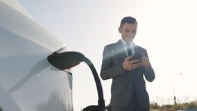 Caucasian businessman using smart phone and waiting power supply connect to electric vehicles for charging the battery