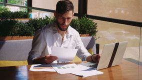 Caucasian businessman working with laptop and documents at table. stock footage