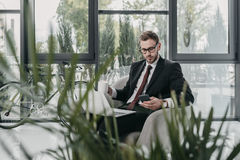 Caucasian businessman working with laptop and smartphone while sitting in modern office. Concentrated caucasian businessman working with laptop and smartphone Stock Photo