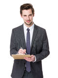 Caucasian businessman write on clipboard Royalty Free Stock Image