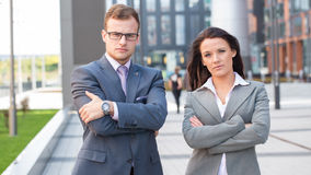 Caucasian businesswoman and businessman standing with crossed  arms on a chest. Royalty Free Stock Photography