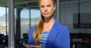 Caucasian businesswoman with digital tablet standing in modern office 4k stock video footage